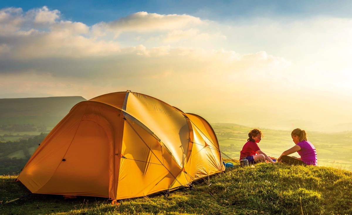 Active children sitting happily beside a colourful dome tent camped high on a green mountain top overlooking the sunlight filled valley below on an idyllic summer evening. ProPhoto RGB profile for maximum color fidelity and gamut.