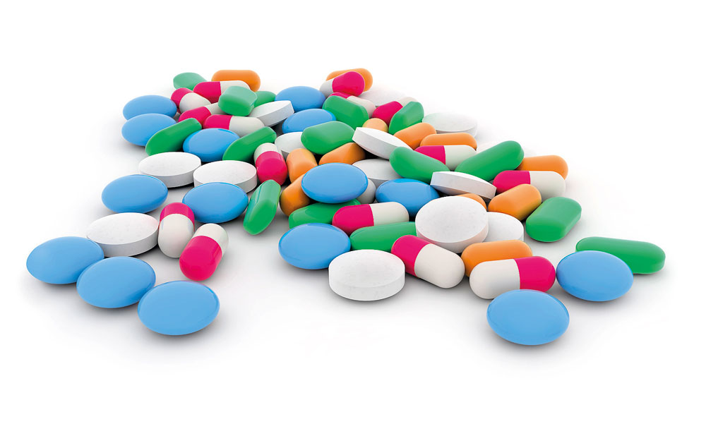 pills and capsules scattered on white background
